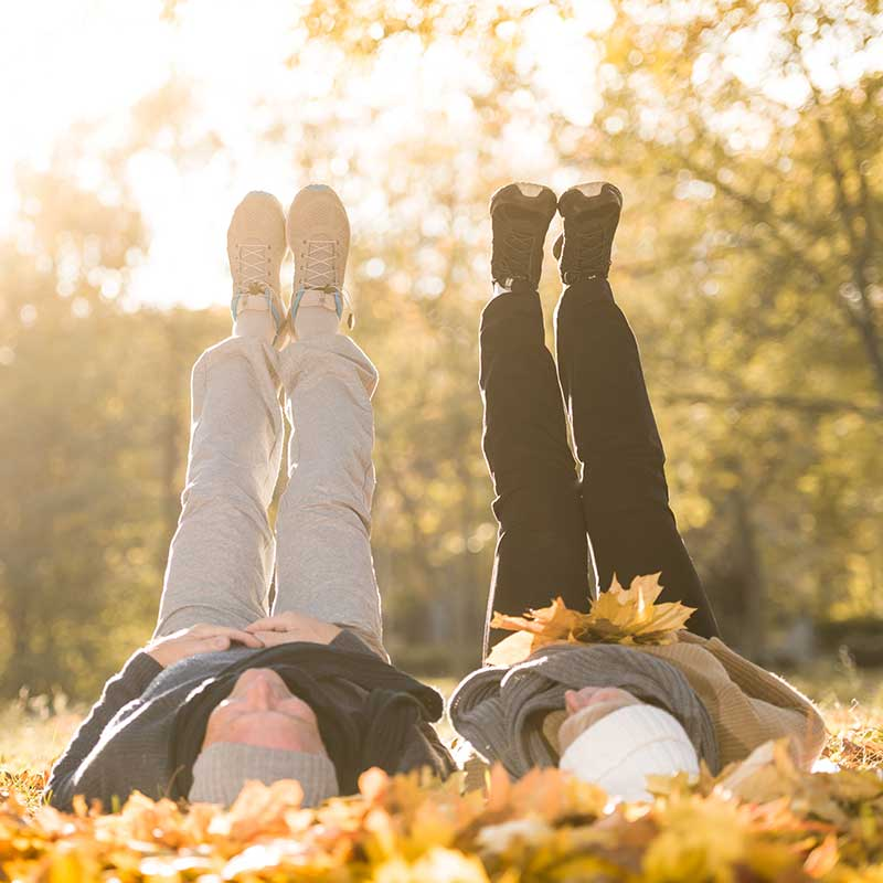 mature couple lying in fall leaves